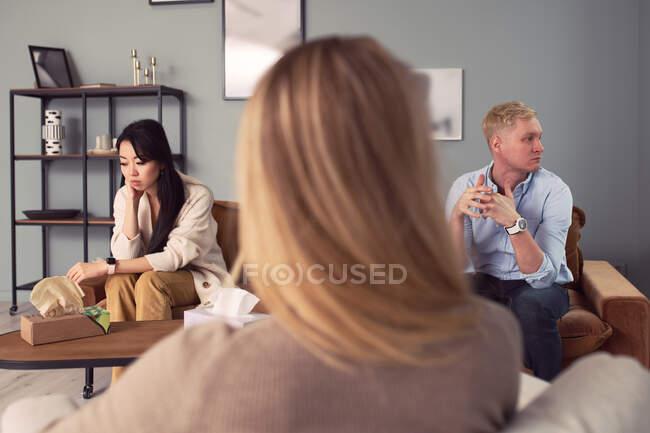 Pareja multiétnica sentada en el sofá y hablando de problemas mentales durante la sesión de terapia con el psicólogo - foto de stock
