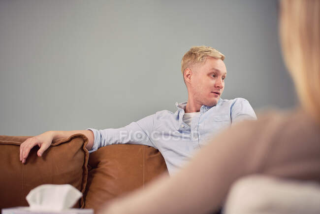 Worried male sitting on couch and speaking during mental psychotherapy session with psychologist — Stock Photo
