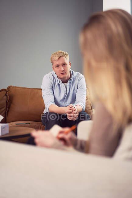 Homem preocupado sentado no sofá e falando durante a sessão de psicoterapia mental com o psicólogo — Fotografia de Stock