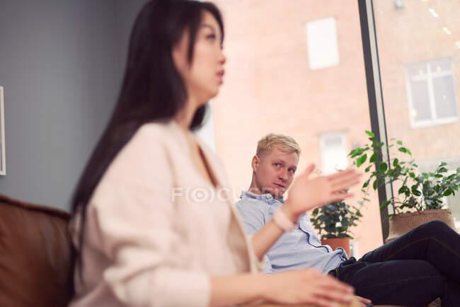 La mujer asiática infeliz tomando al hombre indiferente durante la sesión de terapia en la oficina del psicólogo - foto de stock