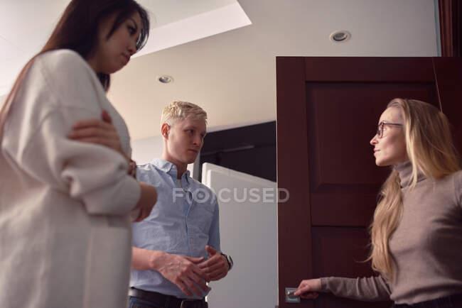 Baixo ângulo de psicólogo feminino em pé na porta do escritório durante a consulta com o casal com problemas no relacionamento — Fotografia de Stock