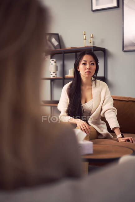 Besorgte Asiatinnen sitzen auf dem Sofa und hören während der psychologischen Therapie auf den Rat eines Psychologen — Stockfoto