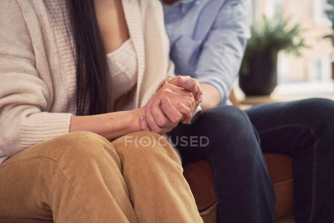 Multiracial couple sitting on sofa in office of psychologist and holding hands during psychotherapy appointment — Stock Photo