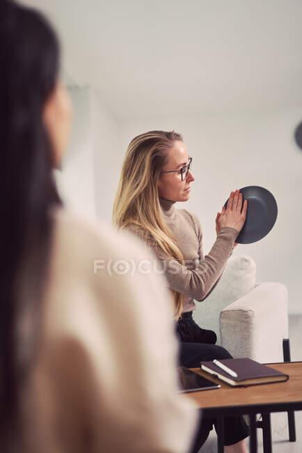 Visão lateral de psicóloga com placa gesticulando e dando conselhos a cliente irreconhecível durante a consulta de psicoterapia — Fotografia de Stock