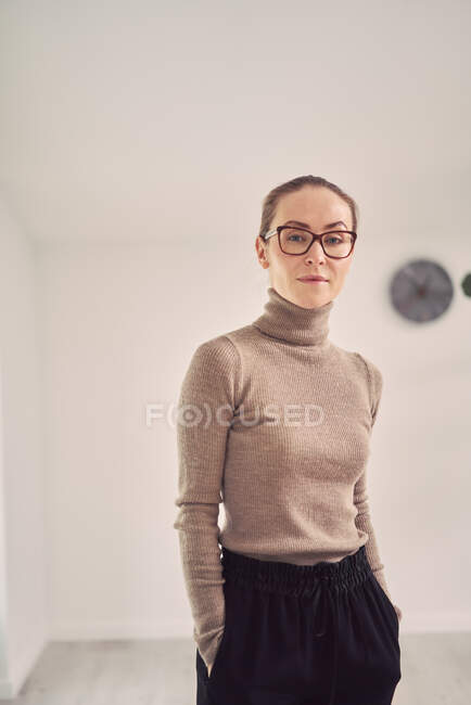 Serious female counselor standing with hands in pockets in office for psychotherapy sessions and looking at camera — Stock Photo