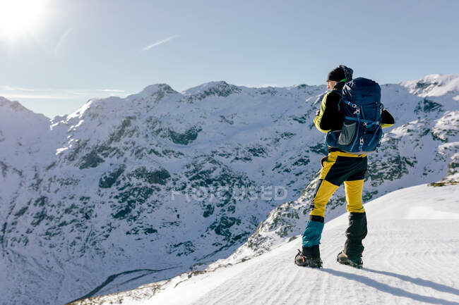 Full body back view of unrecognizable male mountaineer in warm activewear with backpack standing on slope of snowy rocky mountain and enjoying spectacular landscape in sunny winter day — Stock Photo