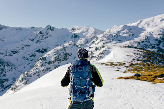 Back view of unrecognizable male mountaineer in warm activewear with backpack standing on slope of snowy rocky mountain and enjoying spectacular landscape in sunny winter day — Stock Photo