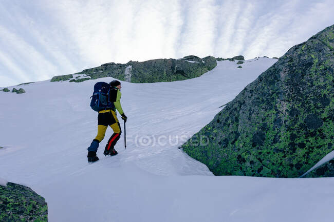 Side view of unrecognizable climber walking on slope of snow covered rocky mountain range in sunny weather — Stock Photo