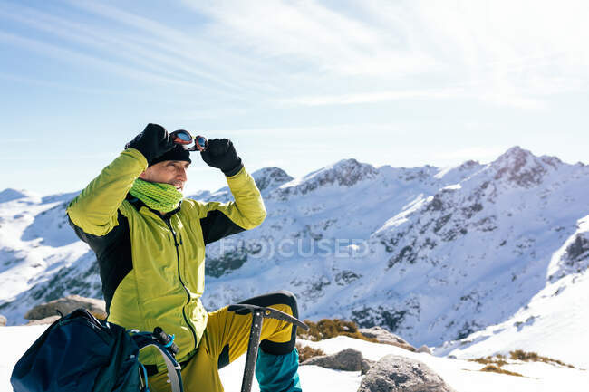 Side view of confident male mountaineer in stylish warm activewear with backpack an climbing equipment standing on top of mountain and looking away while exploring snowy rocky landscape in sunny weather — Stock Photo