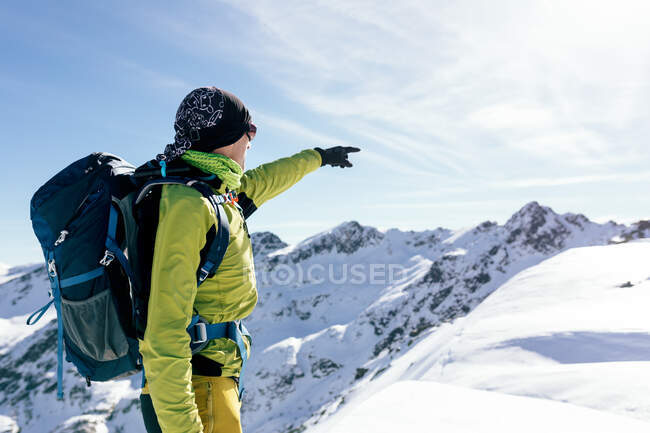 Side view of unrecognizable male mountaineer in warm activewear with backpack standing pointing on slope of snowy rocky mountain and enjoying spectacular landscape in sunny winter day — Stock Photo