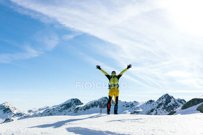Full body of active male mountaineer in colorful activewear raising arms and enjoying freedom while standing on snowy top of mountain against blue cloudy sky in sunny day in highlands — Stock Photo