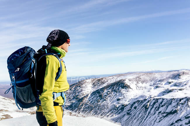 Side view of unrecognizable male mountaineer in warm activewear with backpack standing on slope of snowy rocky mountain and enjoying spectacular landscape in sunny winter day — Stock Photo