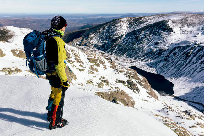 Full body side view of unrecognizable male mountaineer in warm activewear with backpack standing on slope of snowy rocky mountain and enjoying spectacular landscape in sunny winter day — Stock Photo