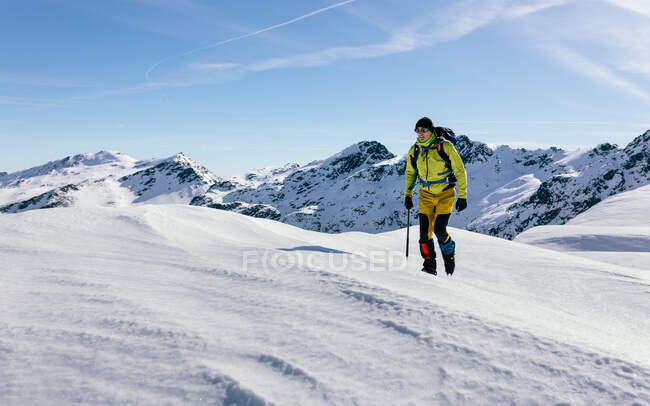 Male climber in outwear walking on slope of snow covered rocky mountain range in sunny weather — Stock Photo
