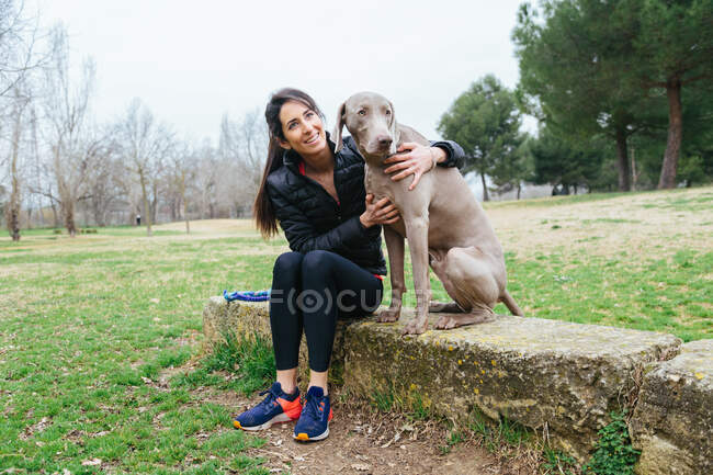 Cheerful female owner embracing loyal purebred Weimaraner dog while sitting together on border on grassy meadow in park — Stock Photo