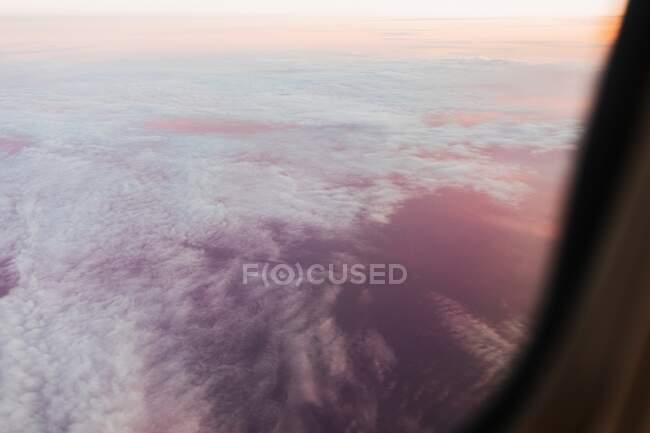 A través de la ventana del avión vista de nubes blancas en el cielo sin fin durante el vuelo al amanecer en Dolomitas Italia - foto de stock