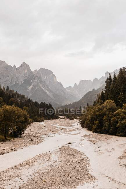Picturesque view of sandy roadway between trees and high mounts under cloudy sky in Dolomites — Stock Photo
