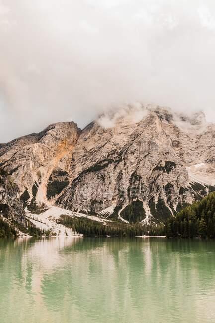 Increíble vista de la cordillera de los Dolomitas con el agua verde del lago que refleja pendientes rocosas ásperas cubiertas de niebla y nubes en Italia - foto de stock