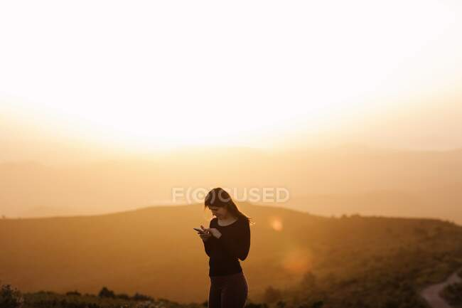 Side view of delighted female browsing mobile phone while standing on hill against mountain under sunset sky — Stock Photo