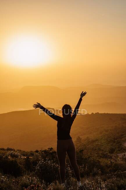Back view of unrecognizable female standing with raised arms on hill and enjoying freedom while admiring mountainous scenery at sunset — Stock Photo