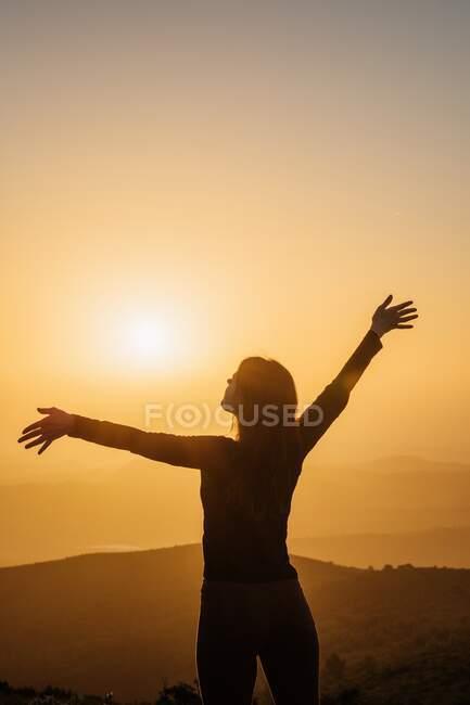 Vue arrière d'une femelle méconnaissable debout avec les bras levés sur une colline et jouissant de la liberté tout en admirant les paysages montagneux au coucher du soleil — Photo de stock