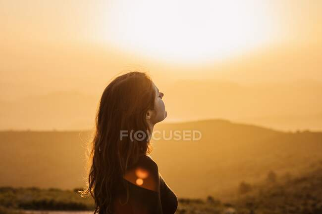 Side view of happy female standing with eyes closed on hill and enjoying freedom while admiring mountainous scenery at sunset — Stock Photo