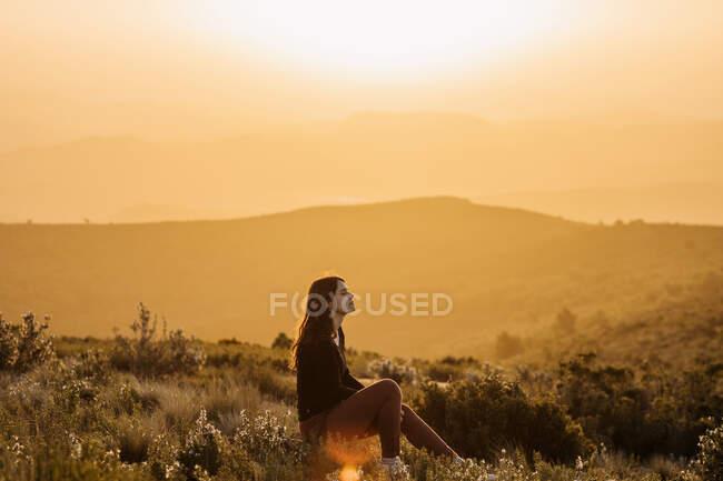 Вид сбоку мирной женщины, сидящей на холме с закрытыми глазами и наслаждающейся природой на возвышенностях на закате — стоковое фото