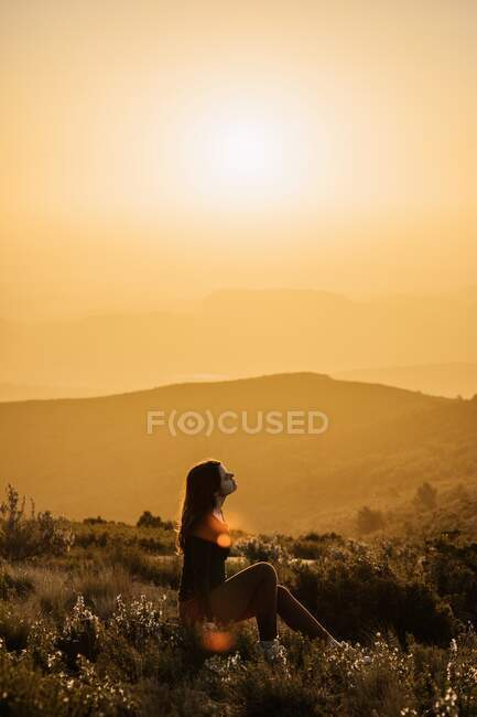Side view of peaceful female traveler sitting on hill with closed eyes and enjoying nature in highlands at sundown — Stock Photo