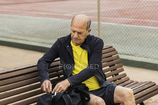 Bald aged male athlete opening bag while sitting on bench on court before tennis training — Stock Photo