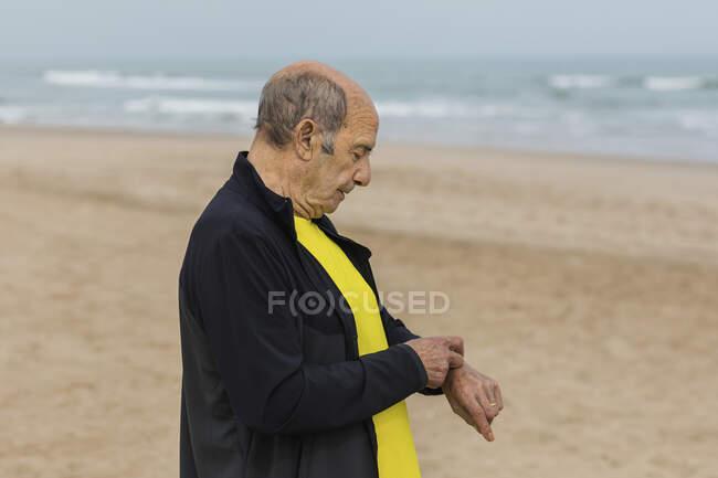 Atleta masculino sênior verificando pulso no relógio inteligente durante o treino de fitness na praia de areia perto do mar — Fotografia de Stock