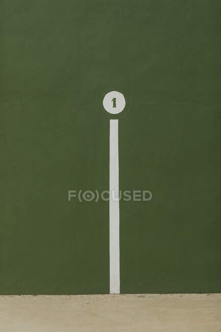 White line and circle with digit 1 depicted on green wall of gym — Stock Photo