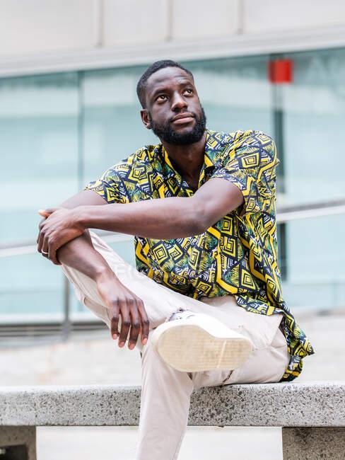 Жалкий этнический мужчина в модной одежде сидит со скрещенными ногами на городской скамейке, глядя вверх — стоковое фото
