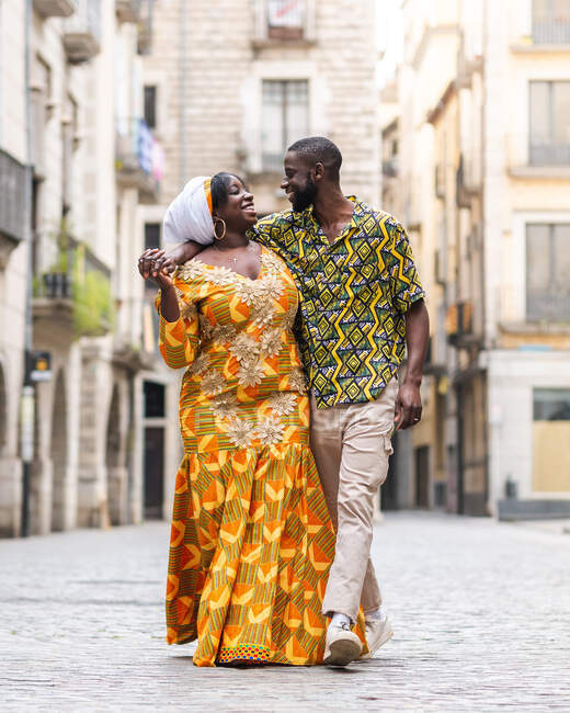 Cheerful black couple in bright outfit with ornament speaking while walking on urban pavement and looking at each other — Stock Photo