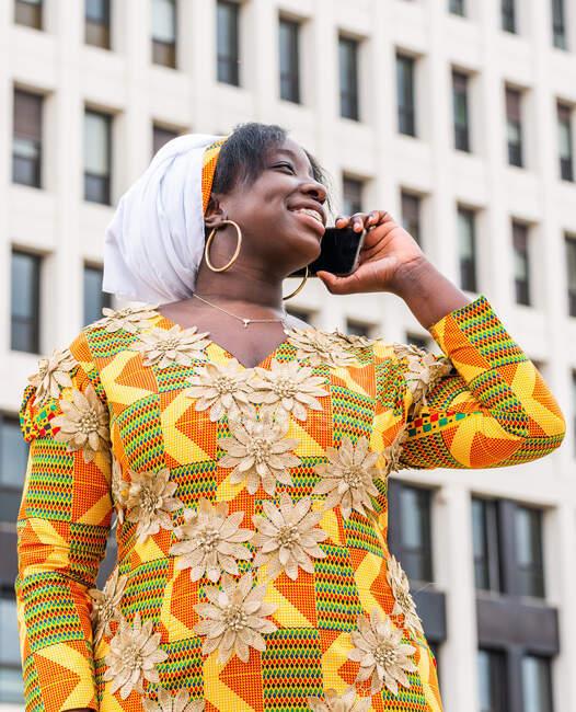 D'en bas de souriante femelle noire en vêtements ornementaux parlant sur téléphone portable tout en regardant loin dans la ville — Photo de stock