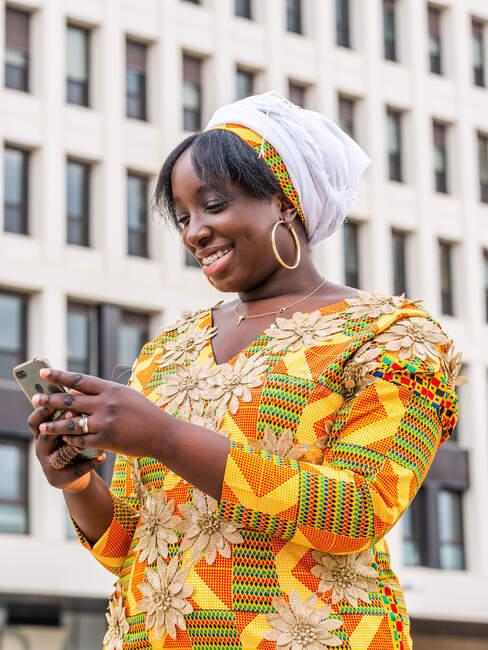 Desde abajo de sonriente hembra negra en ropa ornamental navegando en el teléfono celular mientras está de pie en la ciudad - foto de stock