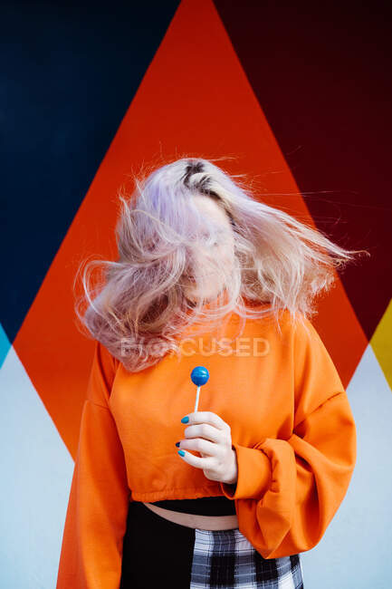 Charming young female in bright clothes with blond hair and lolly looking away in sunlight — Stock Photo