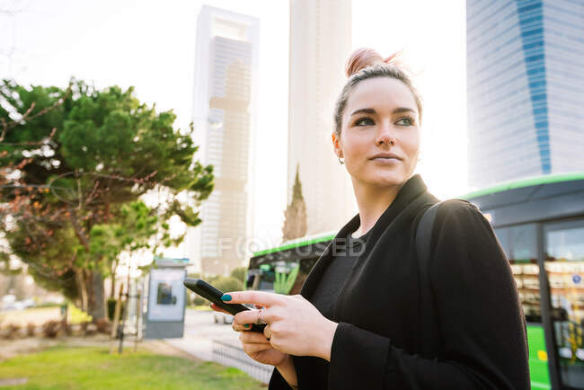 Content young female with cellphone standing on urban pavement and looking away — Stock Photo