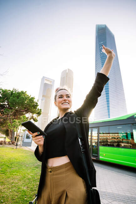 Content young female with cellphone standing with raised arm on urban pavement and looking away — Stock Photo