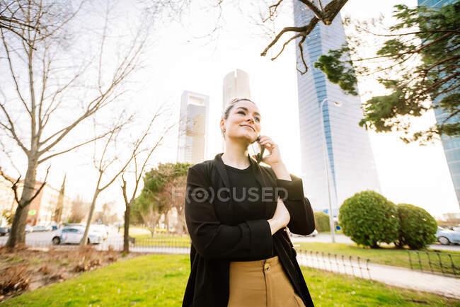 Jeune femme joyeuse avec un chignon à cheveux parlant sur un téléphone portable tout en regardant loin sur la rue de la ville dans le dos éclairé — Photo de stock