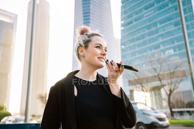 Femme amicale parlant sur téléphone portable et regardant loin dans la rue contre les gratte-ciel modernes en plein jour — Photo de stock