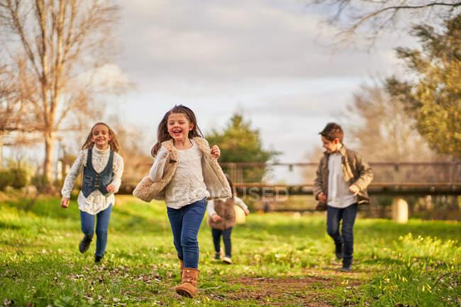 Gruppo di allegri bambini che corrono lungo il prato verde nel parco nella giornata di sole in autunno — Foto stock