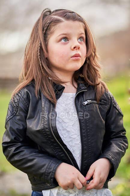 Adorable fille portant veste en cuir élégant debout dans le parc et regardant vers le haut avec intérêt — Photo de stock