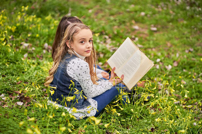 Smart children sitting on green hill in park and reading interesting books while enjoying weekend together — Stock Photo