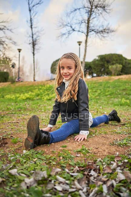 Милая гибкая девушка сидит на газоне в парке и смотрит в камеру — стоковое фото
