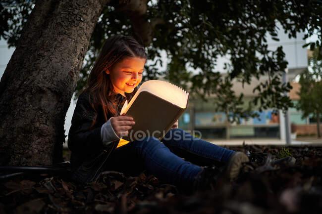 Розумні діти сидять на зеленому пагорбі в парку і читають цікаві книжки під час вихідних. — стокове фото