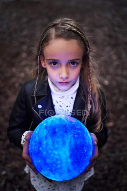 Fille debout dans le parc avec boule mystérieuse rayonnant avec des lumières magiques colorées — Photo de stock