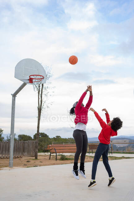 African American boy shoots basket defended by his mother on basketball court — Stock Photo