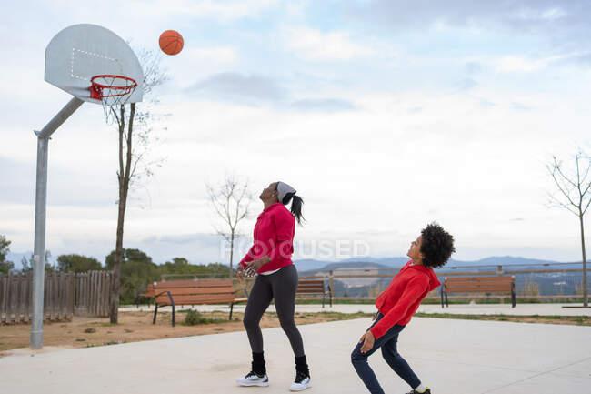 Мать и сын веселятся на открытой баскетбольной площадке — стоковое фото