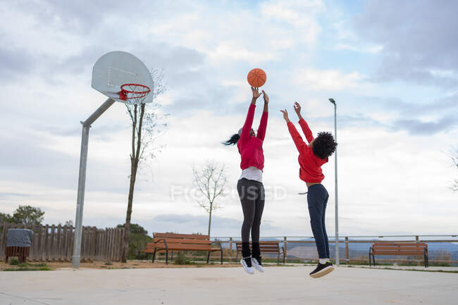 African descendant boy shoots basket defended by his mother on basketball court — Stock Photo