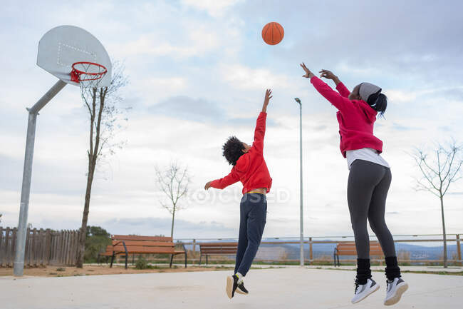 African american mother shoots basket defended by her son on basketball court — Stock Photo